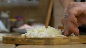 Zakończenie w średnim wieku kobiety ręki ciapania cebule na tnącej desce zbiory