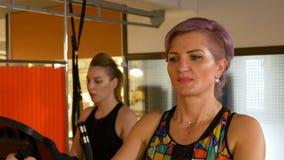 Zakończenie w średnim wieku kobiety utworzenia smartwatch i pracujący out na stepper maszynie przy gym zbiory