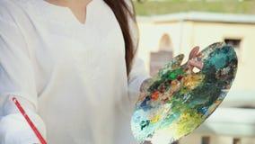 Zakończenie w górę artysta kobiety ręki z szczotkarskim obrazu obrazkiem na kanwie w ulicie na tle modny Sakura zbiory