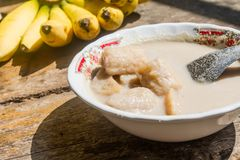Zakończenie w górę banana w kokosowym mleku jest deserowy na stołowym starym drewnianym tle Zdjęcia Stock
