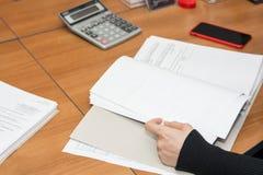 Zakończenie w górę biznesowej kobiety czyta dokumenty przy biurkiem obrazy stock