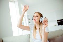Zakończenie w górę fotografii ładnej atrakcyjnej studenckiej młodości nastoletniej apps technologii nowożytną słuchawki słuchać r obrazy royalty free