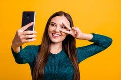 Zakończenie w górę fotografii piękny ostrego ona dama chwyta ręki ręki telefon robi wp8lywy selfies pokazywać palce znaka symbol  zdjęcia stock