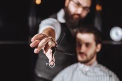 Zakończenie w górę fryzjera męskiego mienia wyposażenia fachowych narzędzi fryzjer - nożyce obraz royalty free
