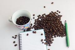 Zakończenie w górę kawowych fasoli dalej i papieru z stołem i Zdjęcia Stock