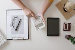 Zakończenie w górę kobiet wręcza podczas gdy używać kalkulatora w biurowym, odgórnym widoku, mockup obrazy royalty free