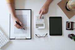 Zakończenie w górę kobiet wręcza podczas gdy używać kalkulatora w biurowym, odgórnym widoku, mockup zdjęcie stock