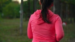 Zakończenie w górę kobieta bieg przez jesień parka przy zmierzchem, tylny widok swobodny ruch zbiory wideo
