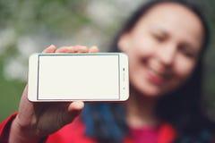 Zakończenie w górę kobiety pokazuje pustego horyzontalnego telefonu ekran na ulicie zdjęcie stock