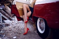 Zakończenie w górę kobiety siedzi wśrodku rocznika czerwonego samochodu na żelaznym usypu tle na iść na piechotę w czerwonych but obraz stock