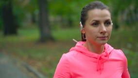 Zakończenie w górę kobiety wybiera muzykę i bieg przez jesień parka przy zmierzchem swobodny ruch zdjęcie wideo