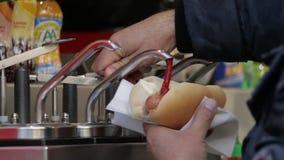 Zakończenie w górę mężczyzna ręki dolewania ketchupu na hot dog zbiory wideo
