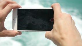 Zakończenie w górę mężczyzna ręki używa mądrze telefon na dennych falach nawadnia błękitnego tło swobodny ruch 1920x1080 zbiory wideo