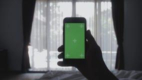 Zakończenie w górę młodego człowieka kłaść na łóżkowym mienia smartphone zieleni ekranu kluczu greenscreen dzielący autentycznego zbiory