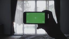 Zakończenie w górę młodego człowieka kłaść na łóżkowym mienia smartphone zieleni ekranu kluczu greenscreen dzielący autentycznego zdjęcie wideo