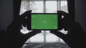 Zakończenie w górę młodego człowieka kłaść na łóżkowym mienia smartphone zieleni ekranu kluczu greenscreen dzielący autentycznego zbiory wideo