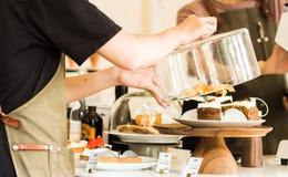 Zakończenie w górę młodego kelnera trzyma szklanego dekiel nad tortem na cakestand przy kontuarem w sklepu z kawą biznesu sklepu  obrazy stock