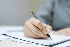 Zakończenie w górę młodej kobiety ręki pisze w notatniku zdjęcia royalty free