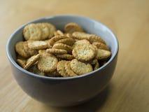 Zakończenie w górę makowego ziarna sezamowych crunchy krakers w szarość rzuca kulą na drewnie Obrazy Stock