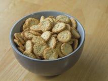 Zakończenie w górę makowego ziarna sezamowych crunchy krakers w szarość rzuca kulą na drewnie Obraz Royalty Free