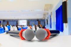 Zakończenie w górę mikrofonu bezprzewodowy starego na stole w konferenci i tło plamy wewnętrznym seminaryjnym pokoju konferencyjn Fotografia Royalty Free