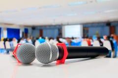 Zakończenie w górę mikrofonu bezprzewodowy starego na stole w konferenci i tło plamy wewnętrznym seminaryjnym pokoju konferencyjn Zdjęcie Royalty Free