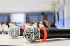 Zakończenie w górę mikrofonu bezprzewodowy starego na stole w konferenci i tło plamy wewnętrznym seminaryjnym pokoju konferencyjn Zdjęcie Stock