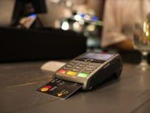 Zakończenie w górę płatniczej maszyny na stole dla płacić rachunek obok przy stołem Bezprzewodowy pos terminal z kart? fotografia stock