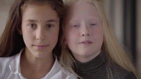 Zakończenie-w górę portret brunetka dziewczyna z brąz oko i blondynka dziewczyna z popielaty oko patrzeć the kamera Poj?cie zdjęcie wideo