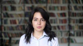 Zakończenie w górę portreta azjatykcia młoda kobieta na tle biblioteczne półki zbiory