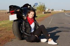 Zakończenie w górę portreta beztroski żeński motocyklista jest ubranym czerni ubrania i biali trenery, siedzą blisko motocyklu, r obrazy royalty free