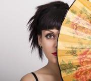 Zakończenie w górę portreta piękna brunetki kobieta zakrywa połówkę twarzy pięknego fan Zdjęcie Royalty Free