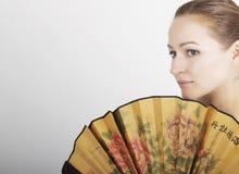 Zakończenie w górę portreta piękna brunetki kobieta zakrywa połówkę twarzy pięknego fan Fotografia Stock