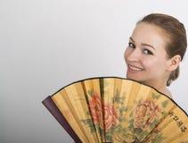 Zakończenie w górę portreta piękna brunetki kobieta zakrywa połówkę twarzy pięknego fan Obraz Stock