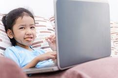 Zakończenie w górę portreta strzału używa laptop azjatykcia mała dziewczynka oblicza obrazy royalty free