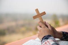 Zakończenie w górę potomstwo ręk trzyma drewnianymi krzyżuje świętą biblię i ono modli się Chrześcijański pojęcie fotografia stock