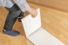 Zakończenie w górę pracownik ręki gromadzić nowego meble na drewnianej podłodze w nowym mieszkaniu h zdjęcie royalty free