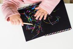 Zakończenie w górę ręk dziecko rysunek na magicznym narysu obrazu papierze z rysunku kijem troszkę fotografia stock