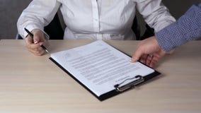 Zakończenie w górę ręk unrecognizable kobiety mienia dokument dołączający schowek i używa pióro podpisywać je - sfałszowany podpi zbiory