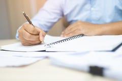 Zakończenie w górę ręka biznesowego mężczyzny pisze rejestrze jest siedzący używać pióro obraz stock