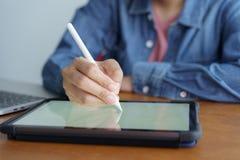 Zakończenie w górę ręki kobiety pracującej pisać na pastylce i pracy Na drewnianym biurka tle laptop obraz royalty free