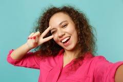 Zakończenie w górę selfie strzału mruganie afrykańska dziewczyna w przypadkowych ubraniach pokazuje zwycięstwo znaka odizolowywaj obrazy stock