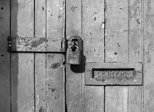 Zakończenie w górę starego drewnianego drzwi z krakingową zatartą farbą i ośniedziałym zamkniętym metalu listowym pudełkiem kłódk obraz royalty free