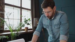 Zakończenie w górę strzału młody człowiek ręki konstruuje otwierać papier i sprawdzać budowa rysunki w architekturze zdjęcie wideo