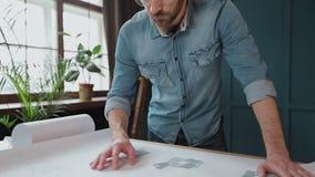Zakończenie w górę strzału młody człowiek ręki konstruuje otwierać papier i sprawdzać budowa rysunki w architekturze zbiory