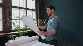Zakończenie w górę strzału młody człowiek ręki konstruuje otwierać papier i sprawdzać budowa rysunki w architekturze zbiory wideo