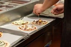 Zakończenie w górę szefa kuchni wręcza sumujących składniki na pizzy na restauracyjnej kuchni zdjęcia royalty free