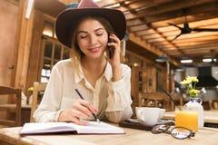 Zakończenie w górę uśmiechniętej dziewczyny w kapeluszowym obsiadaniu przy cukiernianym stołem indoors, opowiadający na telefonie fotografia royalty free