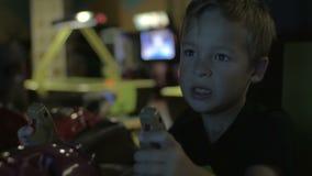 Zakończenie w górę widoku mała chłopiec bawić się wideo arkady grę w gemowym centrum zbiory