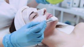 Zakończenie w górę widoku piękna kobieta ma glinianą twarzową maskę stosuje fachowym cosmetologist w piękno zdroju facial zbiory wideo